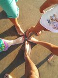 Pies de la familia que se unen en la playa Fotos de archivo