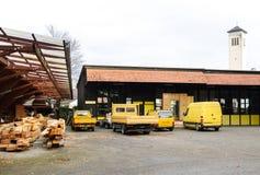 Pies de la fábrica de furgonetas amarillas genéricas en fila delante de la fábrica Fotos de archivo libres de regalías