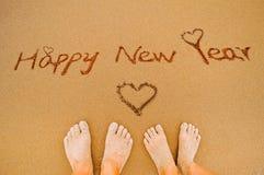Pies de la Feliz Año Nuevo y del amante en la playa Foto de archivo libre de regalías