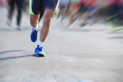 Pies de la gente en el camino de ciudad en raza corriente del maratón Foto de archivo libre de regalías