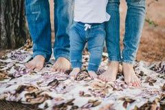 Pies de la madre, del padre y del bebé que llevan vaqueros Imágenes de archivo libres de regalías