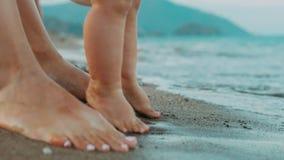 Pies de la madre y del bebé que se colocan en la playa Vacaciones de verano de la familia almacen de video