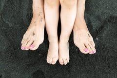 Pies de la mamá y del niño en el primer negro de la arena Imagenes de archivo