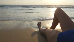 Pies de la muchacha atractiva que mienten en la playa Olas oceánicas que se lavan sobre las piernas y cuerpo femeninos bronceados fotografía de archivo