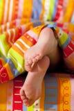 Pies de la muchacha de los niños en una cama bajo el sol de la mañana Foto de archivo