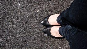 Pies de la muchacha en una tierra del asfalto Fotos de archivo libres de regalías