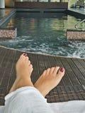 Pies de la mujer al lado de la piscina del balneario Imagen de archivo