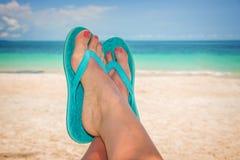 Pies de la mujer con chancletas azules, la playa y el mar Foto de archivo libre de regalías