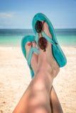 Pies de la mujer con chancletas azules y gafas de sol, playa y mar Imagenes de archivo