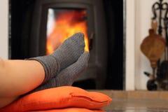 Pies de la mujer con los calcetines que descansan cerca de lugar del fuego Fotografía de archivo libre de regalías