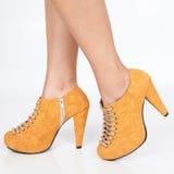 Pies de la mujer con los zapatos de tacón anaranjados con los cordones beige en el fondo blanco imágenes de archivo libres de regalías