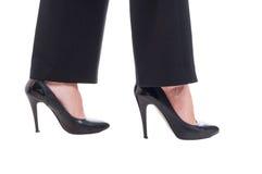 Pies de la mujer de negocios que llevan los zapatos de cuero negros con los tacones altos Foto de archivo libre de regalías