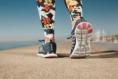 Pies de la mujer del corredor que corren en el primer del camino en el zapato fotos de archivo