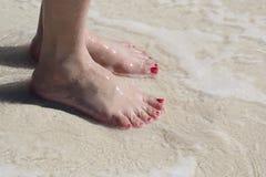 Pies de la mujer en el agua de la playa Imágenes de archivo libres de regalías
