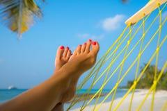 Pies de la mujer en hamaca en la playa Imágenes de archivo libres de regalías