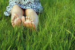 Pies de la mujer en hierba verde Fotografía de archivo libre de regalías