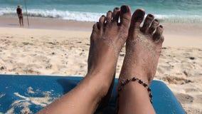 Pies de la mujer en una silla de playa en la playa tropical del paraíso de la isla de Bali, Indonesia