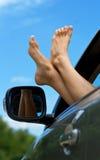 Pies de la mujer fuera de la ventana de coche Fotos de archivo libres de regalías