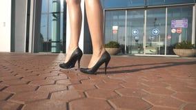Pies de la mujer joven en el calzado de tacón alto que entra en la ciudad Las piernas femeninas en tacones altos calzan caminar e almacen de video