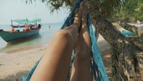 Pies de la mujer joven que mienten en la hamaca en la playa arenosa de la isla en la cámara lenta almacen de video