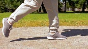 Pies de la mujer mayor que corren a lo largo del camino del parque del verano almacen de video