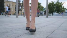 Pies de la mujer de negocios joven en el calzado de tacón alto que entra en la ciudad Las piernas femeninas en tacones altos calz almacen de video