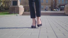 Pies de la mujer de negocios joven en el calzado de tacón alto que entra en la ciudad Las piernas femeninas en tacones altos calz metrajes