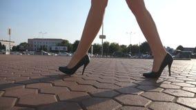 Pies de la mujer de negocios joven en el calzado de tacón alto que entra en la ciudad Muchacha que camina para trabajar Piernas f almacen de video