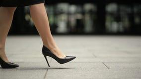 Pies de la mujer de negocios joven en el calzado de tac?n alto que entra en ciudad Zapatos de Legs In High-Heeled de la empresari almacen de video