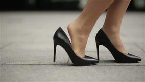 Pies de la mujer de negocios joven en el calzado de tac?n alto que entra en ciudad Zapatos de Legs In High-Heeled de la empresari almacen de metraje de vídeo