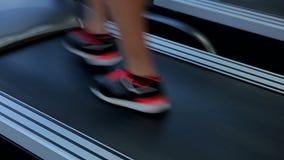 Pies de la mujer que caminan en la rueda de ardilla para calentar antes de entrenamiento activo en gimnasio almacen de metraje de vídeo