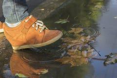 pies de la mujer que caminan en un charco en botas anaranjadas imagenes de archivo