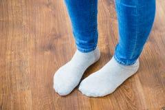 Pies de la mujer que llevan calcetines y los pantalones de los vaqueros fotos de archivo