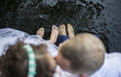 Pies de la novia y del novio en el agua Fotos de archivo