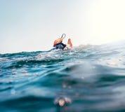 Pies de la persona que practica surf con el cordón de la tabla hawaiana de la seguridad en la cresta de onda foto de archivo libre de regalías