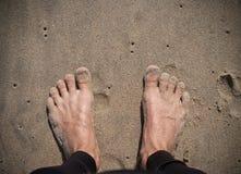 Pies de la persona que practica surf en la arena Fotografía de archivo
