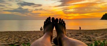 Pies de la puesta del sol en la playa Imagenes de archivo