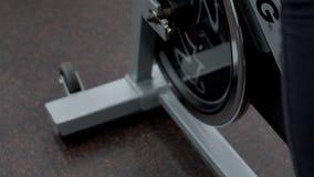 Pies de la señora joven, que está teniendo un entrenamiento en la bicicleta inmóvil en gimnasio moderno, cierre para arriba metrajes
