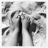 Pies de las muchachas en la arena fotos de archivo