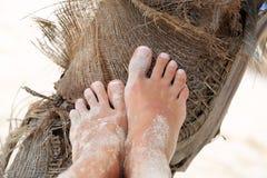 Pies de las muchachas en la arena en la palmera Foto de archivo libre de regalías