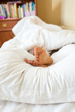 Pies de las muchachas que mienten en la almohada blanca en el dormitorio Foto de archivo