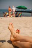Pies de las mujeres en la playa Imágenes de archivo libres de regalías