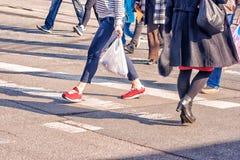 Pies de las mujeres jovenes, cruzando una calle urbana Fotos de archivo libres de regalías