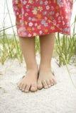 Pies de las niñas en la arena foto de archivo libre de regalías
