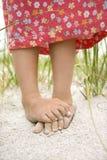 Pies de las niñas en la arena Fotos de archivo libres de regalías