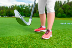 Pies de las señoras y putter del golf en la hierba Fotos de archivo libres de regalías