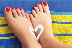 Pies de los adolescentes en una toalla de playa con el corazón del sunlotion Imagenes de archivo