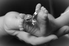 Pies de los bebés en la mano de la mamá con el anillo Foto de archivo