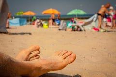 Pies de los hombres en la playa Fotos de archivo