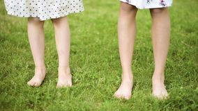 Pies de los niños en hierba verde almacen de metraje de vídeo